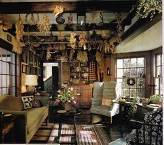 Home Design and Decor , Primitive Living Room Style : Primitive Living Room With Exposed Bemas And Hanging Herbs And Plaid Wingback Chair And Sofa Dn Wooden Coffee Table And Hutch