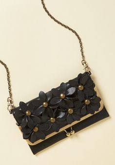 <p>You intentionally make tonight's ensemble simple so that this black clutch can be the center of attention! Filled with floral appliques whose brushed gold centers match the kiss-locked frame of its foldover silhouette, this faux-leather purse puts your elegant tastes in plain sight.</p>