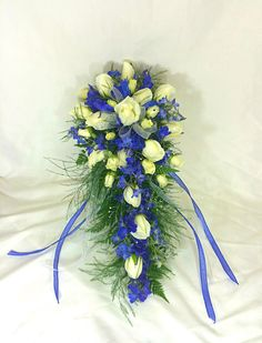 Bridal Bouquet of white roses and blue delphinium with rhinestones and blue and silver ribbons.