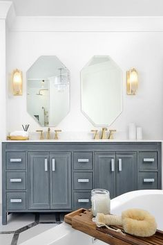 A white and gray octagon floor leads to a gray dual washstand fitted with brushed gold faucets tucked under geometric mirrors lit by glass and brass sconces.