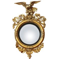 The mirror surmounted by an eagle seated on rock-work over oak leaf and acorn carving, the convex mirror plate with ebonized reeded outer banding and outer ring, the base with shell an leaves.