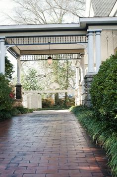 Brick driveway, surrounded by greenery, leading up to a beautiful inviting white home with rich details.