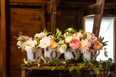 lavender statice white statice white lilies of the valley pink and orange ranunculus or peonies big fluffy flower pompom chrysanthemum roses in anthropologie mugs spelling the love at blue dress barn wedding reception