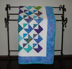 This precious baby quilt is 37 1/2 X 47 and is gender neutral. The colors range from purples to greens and blues. It is the perfect size for a crib or
