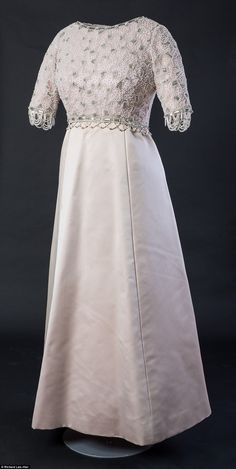 A Hardy Amies ivory dress with intricate beading on the bodice and a simple satin skirt was worn by The Queen during the 1970s