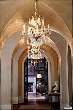 love the architecture of this hallway, and the beautiful chandelier lighting...