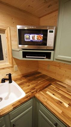 Stainless steel Cuisinart convection microwave providing the ability to not only microwave your food, but also bake and roast without the need for a full-size oven. Electric induction burner in cubby beneath it. Love these countertops! Shenandoah 160 Sq. Ft. Tiny House on Wheels Photo