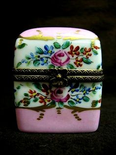 Limoges Porcelain Box with 2 Perfume Bottles Inside. This is a Limoges porcelain box containing two small perfume bottles. It is pink on top and bottom, and has a multicolored floral design with gilt...
