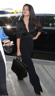 Selena Gomez dons plunging black silk blouse at LAX. Selena Gomez took the plunge in a silky black blouse for her flight out of LAX on … - Selena Gomez Outfits, Selena Gomez Style, Selena Gomez Zimbio, Classy Outfits, Cute Outfits, Women's Black Outfits, Black Slacks Outfit, All Black Outfit For Work, Look Kylie Jenner