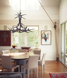 Paul painted the antler chandelier in the dining room, purchased from a friend in Alaska, glossy black. The pulley, selected from Paul's growing collection, is fully functional. The custom-built dining table is ringed by Folio Leather side chairs from Crate & Barrel.  Photo by: Joe Pugliese