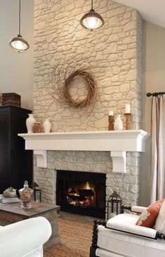 paint fireplace rock out white.  add reclaimed wood mantle or something like this.