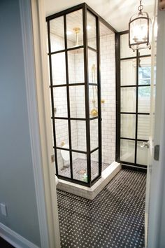 framed glass shower + subway tile shower surround + iron lantern