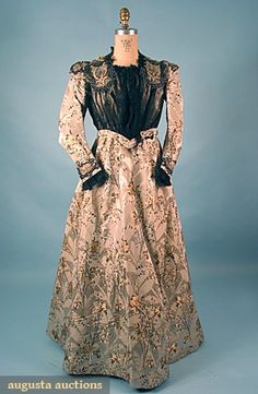 "Afternoon dress, c1898; two piece taupe faille and silver satin figured dress brocaded with gold & black floral sprays, bodice w/ elaborate beaded & lace applique trim & pleated black silk chiffon, label, ""E.E. Chapman Roxbury"", B 40"", W 29"", Front Skirt L 43"", Back Skirt L 45"""