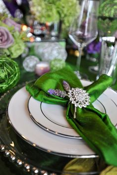 This bold emerald table setting could be used for a lot of celebrations.The glass charger plates and sparking napkin ring give it that special look, while the lavender is the happy medium that pulls it together.