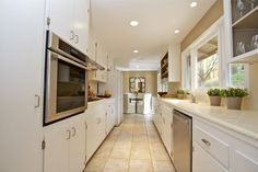 The kitchen features tile countertops, stainless steel appliances and recessed lights. Photo: Karin Larson Photography