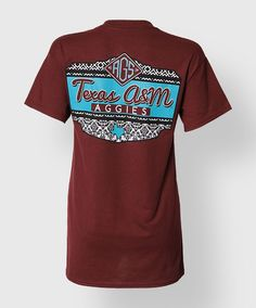 "This maroon shirt has a patterned back with the text ""Texas A&M Aggies"". The front has a faux pocket with a black and white pattern and a blue block ATM."