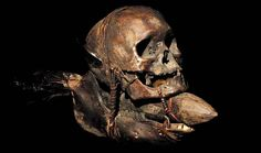 IFUGAO TRIBE: HEADHUNTED HUMAN TROPHY SKULL  MOUNTED ON THE LOWER JAW OF A BOVINE  HUMAN BONE, FEATHERS, RATTAN, WOOD  THE IFUGAO TRIBE, FROM THE PHILIPPINES,  MOUNT TROPHY SKULLS OF THEIR  HEADHUNTED HUMAN VICTIMS.