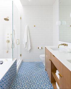 Base branca, acessórios dourado, madeira e ladrilho hidráulico azul! Criação charmosa do escritório Bestor Architecture (@bestorarchitecture), que tal? Veja mais detalhes do espaço no site (link na bio). #casavogue #decoração #banheiro
