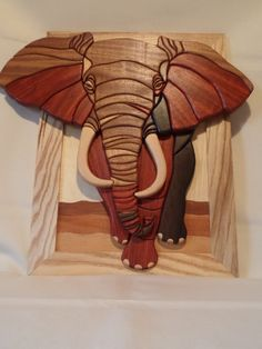 "This wooden intarsia African elephant has been handmade by me using eleven different woods for a beautiful contrast and effect. When i get round to making another the look will change with each one with a slight change in different wood species and grain patterns but still create a stunning piece of wooden intarsia wall art or home decor. The original pattern is the work of Steve Bundred. The African elephant measures 554mm wide x 530mm high or approximately 21 1/4"" x 21"". Ready to..."