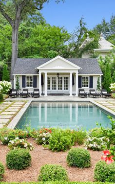 Classic Hamptons style pool house with cream siding, white trim and blue shutters.