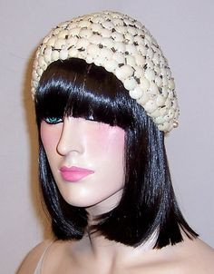 This is a rare and unusual 1920s white skull cap made from hundreds of convex pieces, each a little bit smaller than a dime, of an early plastic type material, interspersed with glass bugle beads and the occasional pearl. The hats interior is made of straw and is lined in tulle. Its label is present and in tact and reads, Busche Hats-New York. This extraordinary millinery creation is in excellent vintage condition, consistent with its age and use, and its circumference measures 22.