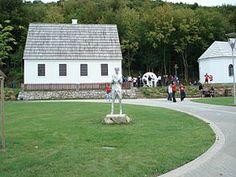 Родна кућа Николе Тесле у Смиљану лево, испред споменик и десно храм СПЦ.