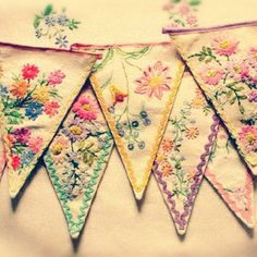 I can't get to the original source - invalid, but it looks as though this bunting may be created from vintage embroidery - ie repurposed tablecloths etc.