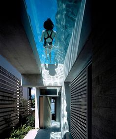 entrance is directly under the lap pool creating an almost magical aqueous light that is transmitted to the entrance area through the water and glass bottom of the pool.