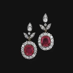 PROPERTY OF A PRINCESS PAIR OF VERY IMPORTANT RUBY AND DIAMOND PENDENT EAR CLIPS. Each suspending a cushion-shaped ruby, weighing 11.46 and 11.64 carats respectively, set within a surround of cushion-shaped and circular-cut diamonds, to a surmount of foliate design embellished with similarly cut and rose diamonds, screw back fittings. Estimate      $1,479,800 - $2,462,810 LOT SOLD. $3,520,339