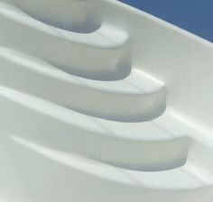 Closeup of the curvy steps of a small fiberglass pool shell with blue sky in the background
