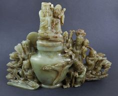 """Green jade lidded vessel in detailed openwork carving, featuring scholars, musicians, court figures, auspicious animals and symbols. Russet brown and white suffusion. 8""""H x 11""""W"""