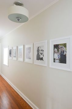 Clean, simple white frames make a beautiful statement in this long hallway