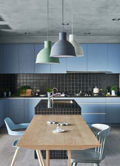 light wood dining table with blue chairs and matte pendant lighting