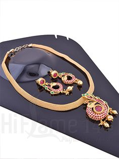 RENT : Classy Gold Plated Pendant Necklace Set.  A splendid designer pendant necklace set that is sure to accentuate your style statement. This pendant necklace is decorated with a beautiful pendant with a peacock design enhanced with pink and green stones with matte finish that is matched with a mesh designed chain, comes with matching earring. Flaunt your traditional wear with this amazing design.