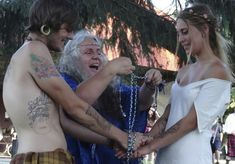 Selena Fox ties the handfasting cords during this couples wedding ceremony at a Pagan Spirit Gathering.