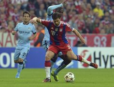Toure is beaten to the ball once again by Xabi Alonso.