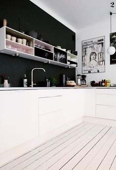 Cuisine noir/ blanc avec quelques touches colorées dans les étagères suspendues