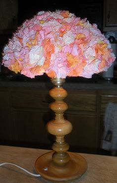 Coffee filter lamp shade in peach, pink, yellow and orange tye-dyed tones.  It looks like hundreds of carnations.  Unlit.