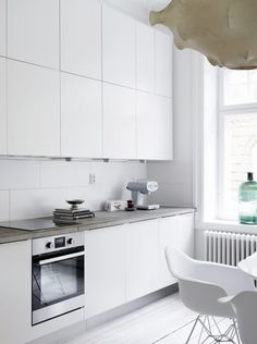 Love this apartment. The bright white kitchen with the concrete worktop together with white painted floors, nice doors and gorgeous windows. And it looks so fab, styled with this. Refacing Kitchen Cabinets, Modern Kitchen Cabinets, New Kitchen, Kitchen Interior, Kitchen Dining, Kitchen Decor, Kitchen White, Kitchen Dresser, Kitchen Worktop