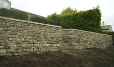 The finished structure is topped with sawn sandstone copings and a stone staircase creates access to the lower level whilst breaking up the visual impact of the wall. Retaining Wall Steps, Landscaping Retaining Walls, Yard Stones, Paving Stones, Landscape Plans, Landscape Design, Contemporary Garden Design, Hillside Garden, Dry Stone