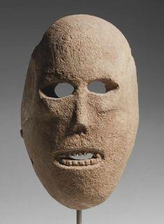 Máscara antigua, pre-cerámica neolítica, encontrada en el desierto de Judea. De piedra caliza (22,8 cm de largo), ca. 7° milenio a.C.; modelada para parecerse a un cráneo humano, de forma ovalada, paredes gruesas y cóncava atrás, ojos recortados con crestas estrechas, pómulos levantados, de nariz triangular y delgada con dos ranuras de fosas nasales, la boca ovalada abierta sin labios, muestra sus dientes, con cinco pozos de perforación bicónicos lo largo del perímetro
