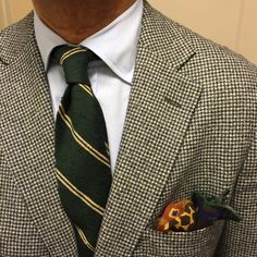 Light grey houndstooth tweed sport coat, light blue shirt, green tie with yellow stripes, navy pants