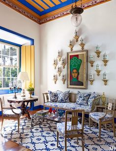 In a sitting room, antique pharmacy jars surround a Lula Cardoso Ayres painting. A Stroheim fabric cushions the Portuguese painted furniture, which is arranged on a By Kamy carpet | archdigest.com