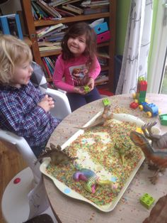 The dinosaur train inspired this rainbow rice play with dinosaurs and a duplo train