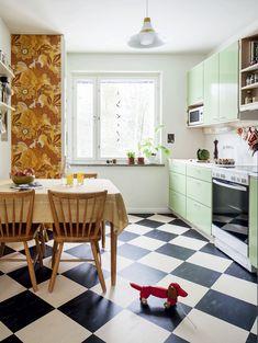 Borås Tapeterin tapetissa hehkuu oranssi. Tapetin on suunnitellut Hanna Werning. Pöytäryhmä ja valaisin on peritty mummilta. Ikkunalaudalla kasvaa muun muassa roseepippuri, jonka siemenet on tuotu Espanjasta. Ainon punainen lelukoira on lahja kummitädiltä. Uuni on Rosenlewin.