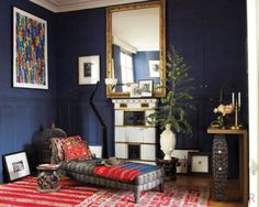 In the entrance room of this colorful Parisian home, the console is sheathed in leather and mussel shells, and the chaise longue is upholstered in a Donghia fabric. The pillows and throws are made from antique Pakistani fabrics, the stool is African, the lithograph is by Jean Cortot, and the porcelain fireplace is late 19th century. See the rest of the home.