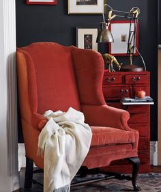 Red velvet arm chair in sitting room with red wooden dresser, patterned rug and framed art on walls: Soft materials—rich velvet upholstery and a luxe alpaca throw—clustered with hard, shiny surfaces create intriguing tactile interplay (sort of makes you want to pet the furniture). Don't be afraid to tuck a big, generous chair into a snug nook for an intimate reading spot.