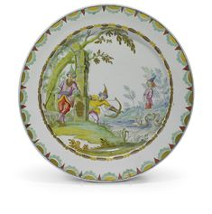A very rare Vezzi plate, circa 1725 painted probably by Duramano with archers hunting swans beside ruined building on the banks of a river, the rim with borders of cabochons and pearls in brown and gold, and half-ovals in brown, green and gold, the reverse incised with A and N
