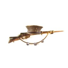 Yellow metal rifle and hat brooch. Yellow metal rifle and hat brooch. With three paste accents. Length 50 mm. Weight 4.4 grams. In fitted box.