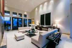 Soaring ceilings highlight the custom wall of marble in the formal living room and showcases beautiful fairway views that surround the home. Clean lines, neutral tones and sophisticated design create an aesthetically soothing environment that flows from room to room.